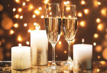 Champagne glasses and candles against blurred lights background, space for text
