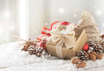 Christmas presents or gifts with elegant bow and christmas decorations on bright snowy background, christmas concept